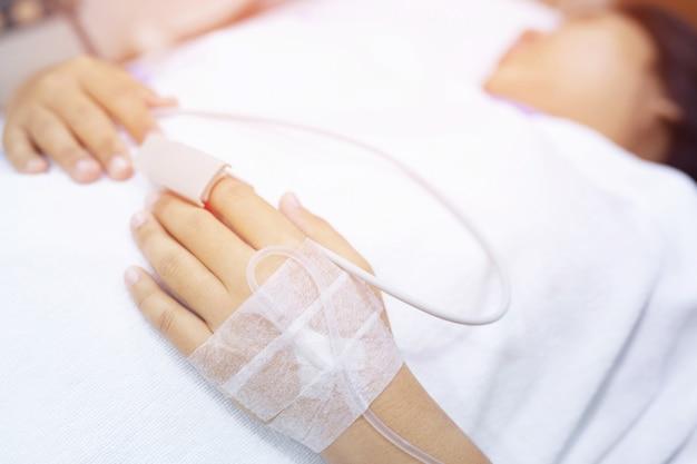 Feche o foco de pessoas na mão de um paciente doente na cama na enfermaria do hospital. saúde e médico