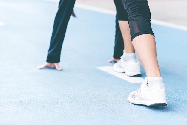 Feche o foco seletivo pé de mulher com um tênis na pista de corrida se preparando para começar.