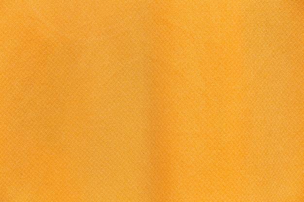 Feche o fundo e a textura de pano de tecido amarelo.