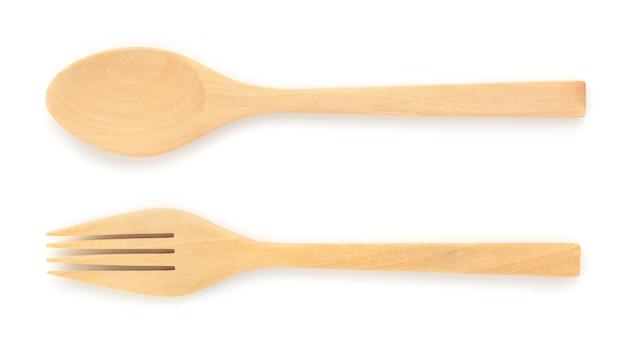 Feche o garfo de madeira e a colher isolados na superfície branca