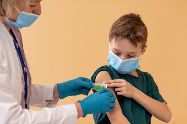 Feche o garoto e o médico usando máscaras