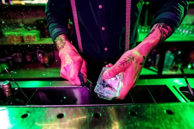 Feche o grande pedaço de gelo derretido no balcão do bar em chamas de fogo, preparando-se para um coquetel