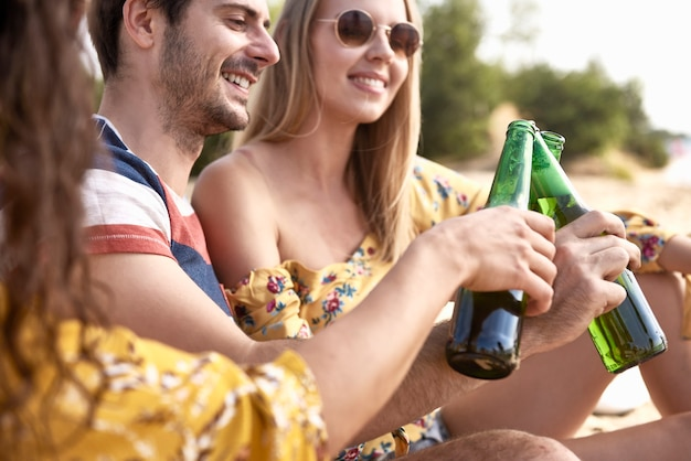 Feche o grupo de amigos fazendo um brinde comemorativo com cerveja
