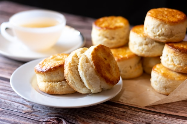 Feche o grupo de frescos saborosos deliciosos scones britânicos tradicionais e uma xícara de chá na mesa de madeira.