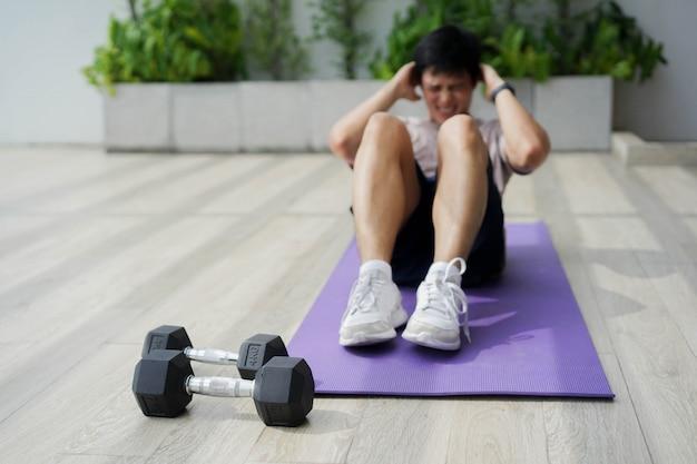 Feche o haltere com o jovem sentado no chão para treinar sozinho pela manhã