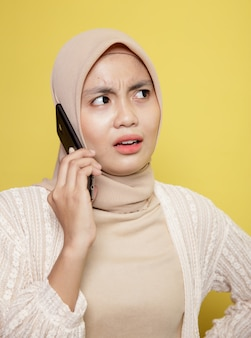 Feche o hijab de mulher com uma expressão de telefone chamando isolada em fundo amarelo