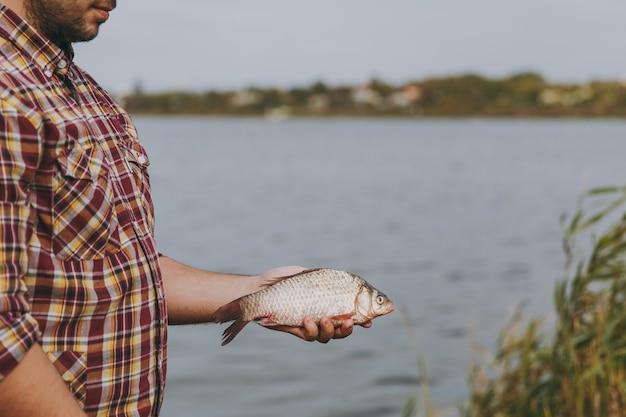 Feche o homem com a barba por fazer na camisa quadriculada com mangas arregaçadas, pegou peixes, segura-o nos braços na margem do lago no fundo da água, arbustos, juncos. estilo de vida, recreação do pescador, conceito de lazer.