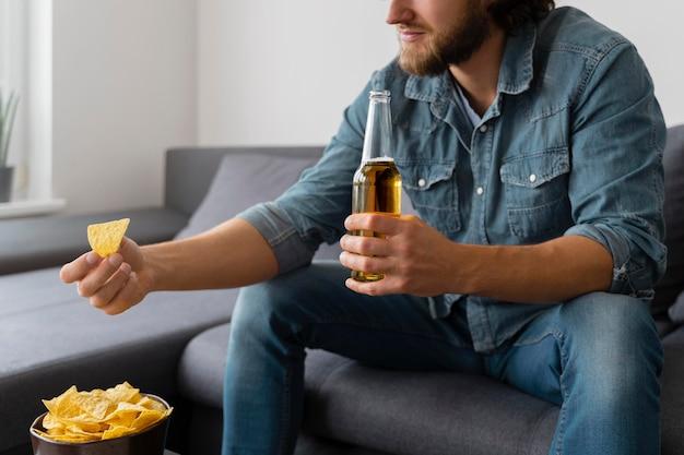 Feche o homem com batatas fritas e beba