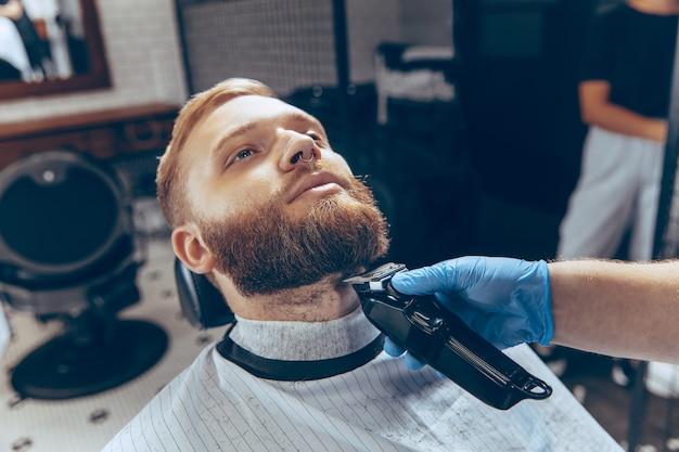 Feche o homem cortando o cabelo na barbearia usando máscara durante a pandemia de coronavírus.