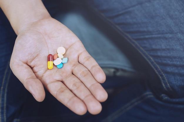 Feche o homem de mão tomando comprimidos de várias cores na mão. pare o uso de drogas, conceito médico de cuidados de saúde tomando medicamentos