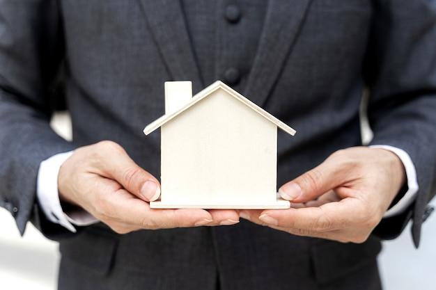 Feche o homem de negócios asiáticos segurando a casa modelo - conceito de finanças empresariais.