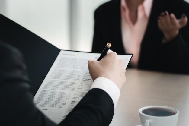 Feche o homem de negócios, escrevendo ou assinando contrato em papel no escritório.