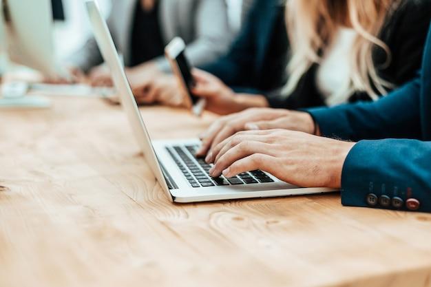 Feche o homem de negócios trabalhando em um laptop no escritório