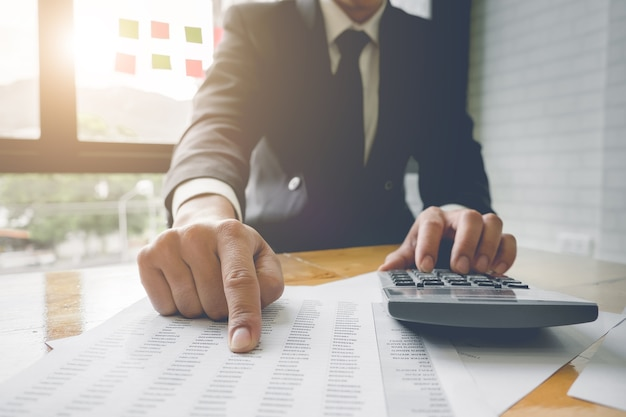 Feche o homem de negócios usando a calculadora e apontando dados do documento para calcular, fiscal, contabilidade, conceito contábil.
