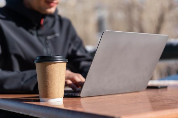 Feche o homem digitando no laptop