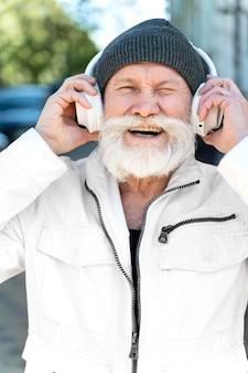 Feche o homem feliz usando fones de ouvido