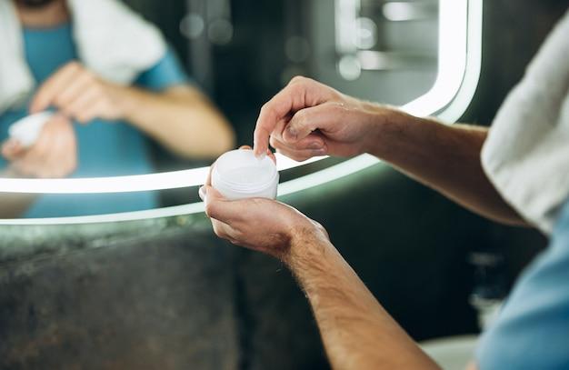 Feche o homem foto segurando creme hidratante para o rosto no banheiro de manhã cedo.