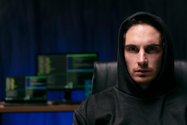 Feche o homem misterioso com computadores