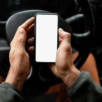 Feche o homem no carro com o celular