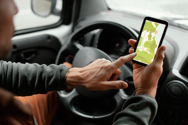 Feche o homem no carro com o mapa no celular