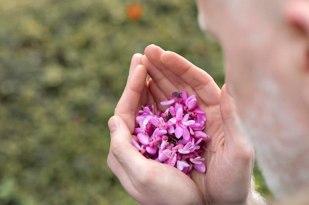 Feche o homem segurando lindas flores