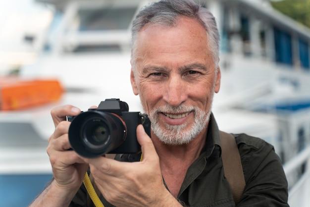 Feche o homem sorridente com a câmera