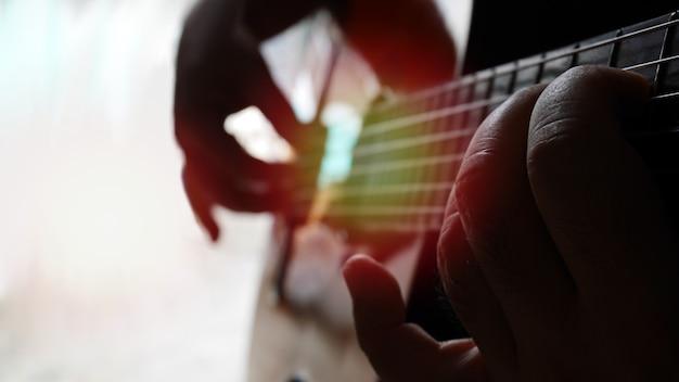 Feche o homem tocando violão, sua mão direita toca acorde de escala e a mão esquerda toca corda