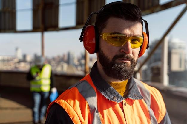Feche o homem usando fones de ouvido e óculos de proteção