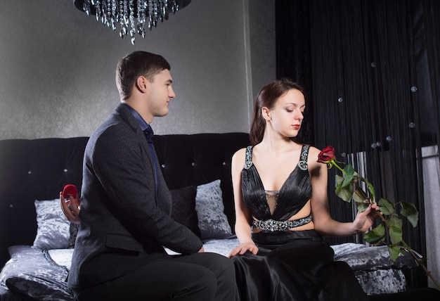 Feche o jovem casal em trajes elegantes, sentado no quarto, enfatizando a linda mulher segurando uma flor de rosa vermelha.
