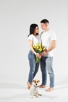 Feche o jovem casal retrato com flores amarelas. casal adorável abraçando com expressão sonhadora amorosa. comemorando o dia dos namorados, dia da mulher.