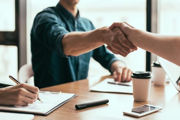 Feche o jovem empresário apertando a mão de seu parceiro de negócios