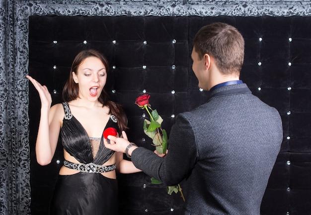 Feche o jovem namorado oferecendo um anel e uma flor rosa para a namorada com uma reação de surpresa.