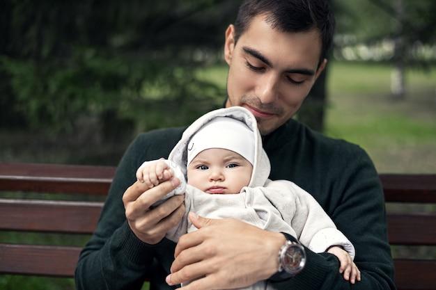 Feche o jovem pai em um macacão verde com um bebê nos braços, sentado no banco do parque
