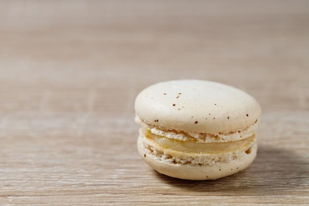 Feche o macaron de bolo ou macaroon em um fundo de madeira com espaço de cópia, sobremesa doce