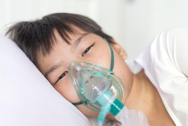 Feche o menino asiático yong doente com máscara de oxigênio facial deitado em uma cama branca no hospital.