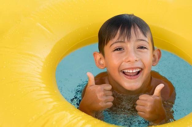 Feche o menino sorridente com a bóia salva-vidas