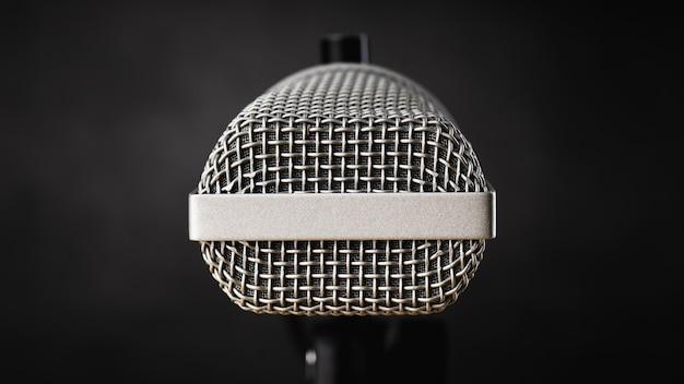 Feche o microfone para gravação de áudio ou conceito de podcast, microfone único em fundo de sombra escura com espaço de cópia