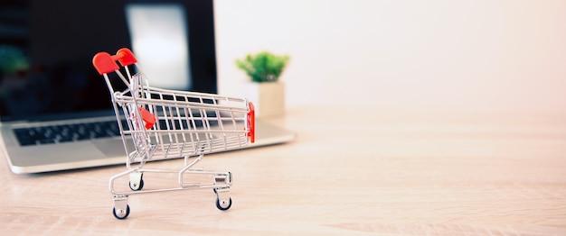 Feche o mini carrinho de compras e o laptop na mesa.