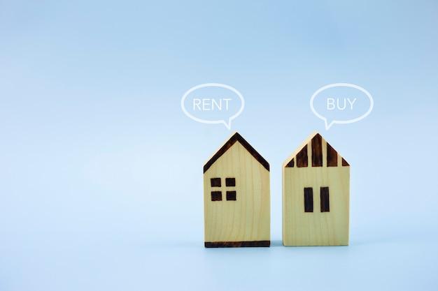 Feche o modelo da casa com comprar ou alugar em fundo azul pastel