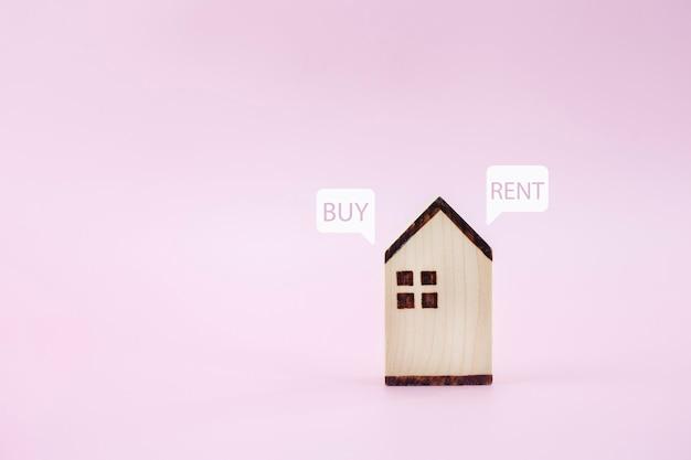 Feche o modelo da casa com comprar ou alugar em fundo rosa pastel