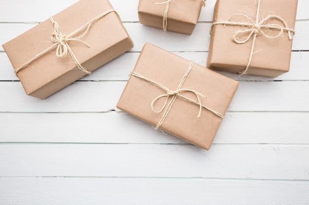 Feche o pacote de papel marrom rústico do estilo do natal amarrado com cordas. fundo de madeira branco.