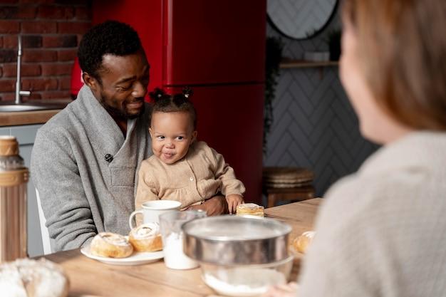 Feche o pai feliz segurando as crianças na mesa