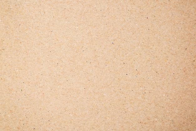Feche o papelão reciclado ou o fundo da textura da caixa de papel do ofício da placa marrom.