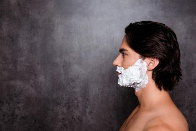 Feche o perfil lateral do homem com espuma branca no rosto