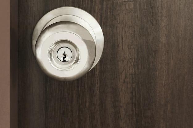 Feche o punho de metal em uma porta de madeira velha, trava de segurança do botão moderno.
