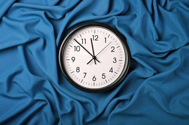 Feche o relógio clássico de parede branca sobre um fundo azul de tecido com pregas de tecido dobradas, vista superior elevada, diretamente acima
