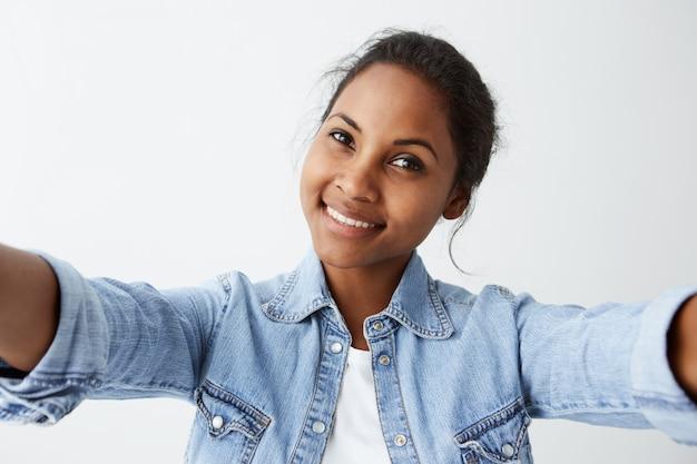 Feche o retrato altamente detalhado da atraente mulher afro-americana bonita, com cabelos pretos e pele escura, vestida casualmente com uma expressão agradável e um sorriso encantador.