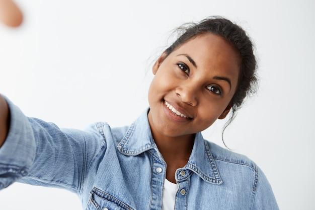 Feche o retrato altamente detalhado da encantadora jovem afro-americana com cabelo preto e perfeita pele escura saudável, vestindo camisa jeans azul clara, com um sorriso bem fofo.