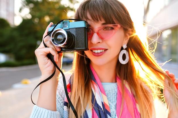 Feche o retrato ao ar livre da cidade de uma linda jovem magnífica segurando a câmera de filme vintage retrô, usando óculos escuros de suéter pastel e lenço, luz do sol da noite.