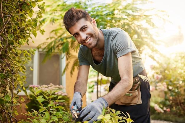 Feche o retrato ao ar livre de um belo alegre fazendeiro barbudo caucasiano com camisa azul e luvas sorrindo, trabalhando com ferramentas de jardim em sua fazenda perto de casa de campo